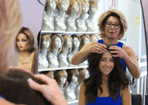 Caryl Criscio at Wigful Thinking Wig Studio helping young woman try on a human hair wig.